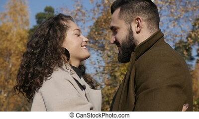 Hugging couple walking in park