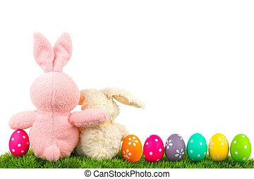 Hugging Easter bunnies on grass with colorful egg border...