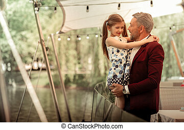 Cute daughter wearing nice dress hugging her loving father