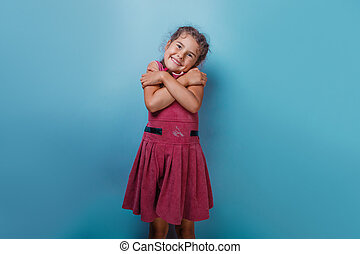 hugging herself on a blue background - Girl European...