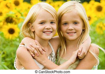 Hugging sisters - Portrait of cute twins embracing each...