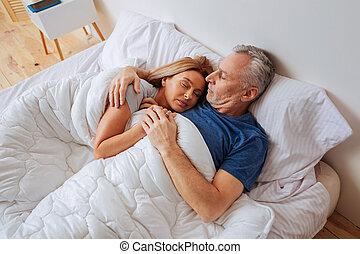 Loving caring husband hugging his beautiful sleeping wife