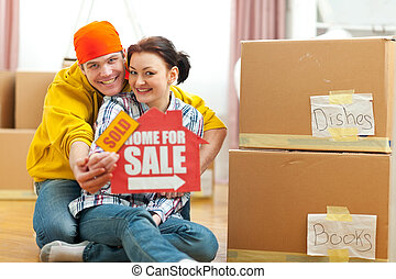 Hugging young couple showing home for sale sign with sold sticker