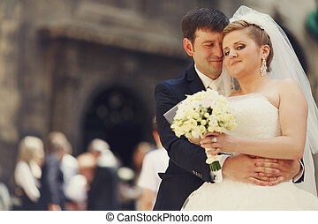 Hugs and smiles - groom stands with eyes closed