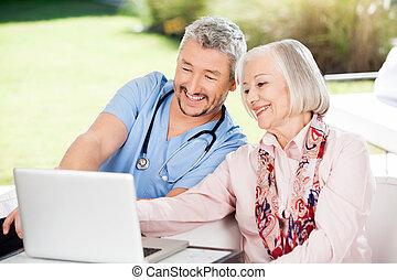 huisbewaarder, en, oude vrouw, gebruikende laptop
