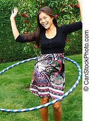 Hula hoop. Beautiful young woman doing hula hoop outdoors in...