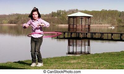 hula hoop - little girl hula hooping near a lake