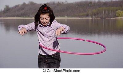 hula hooping - little girl hula hooping near a lake