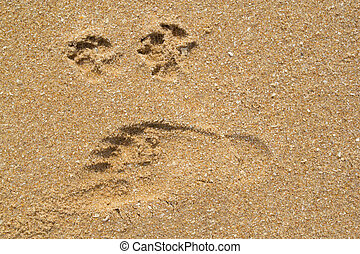 Human and dog footprints on the sandy beach.