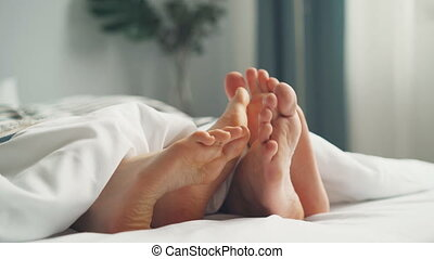 Human bare feet touching each other in bed under white...