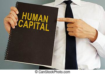 Human Capital concept. Manager holding book.