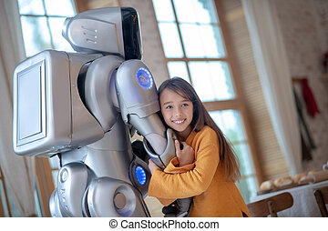 Cute girl feeling good with her robot friend