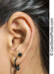 Human ear closeup with metal earring