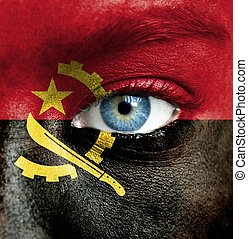 Human face painted with flag of Angola