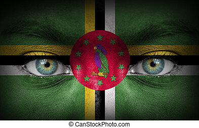 Human face painted with flag of Dominica