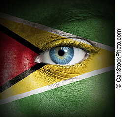 Human face painted with flag of Guyana