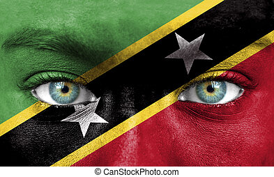 Human face painted with flag of Saint Kitts and Nevis
