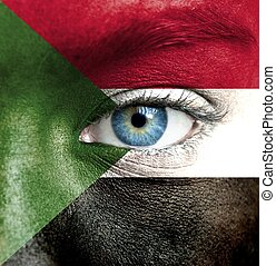 Human face painted with flag of Sudan