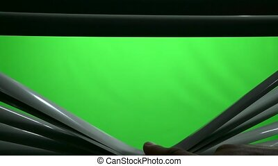 Human finger in the dark opens the jalousie. Green screen