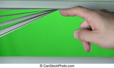 Human finger raises the white jalousie up. Green screen