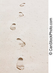 Human footprints leading towards the viewer. Copyspace on right