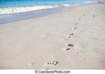 Human footprints on white sand beach - Human footprints on ...