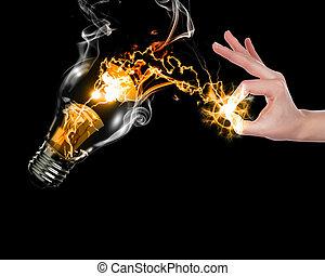 human hand and bulb - human hand, electric charge and light...