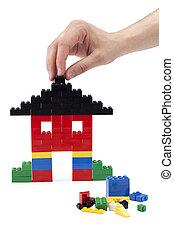 human hand and lego house