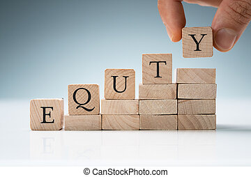 Human Hand Arranging Blocks In A Row Showing Equity Text
