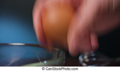 Human Hand Breaking an Egg - Human hand breaking an egg into...