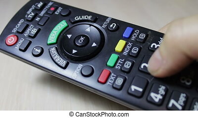 human hand changes the channels on the TV remote control