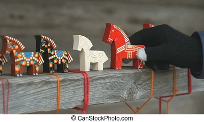 Human hand choosing one traditional horse toy - Human hand...