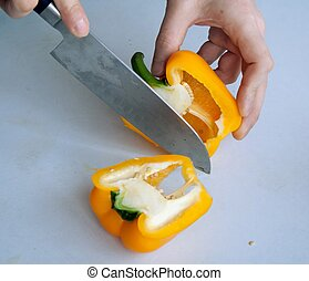 Human hand cutting pepper with knife