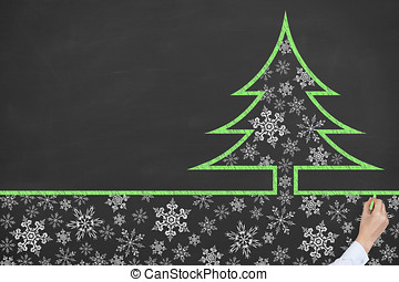 Human Hand Drawing Christmas Tree on Chalkboard
