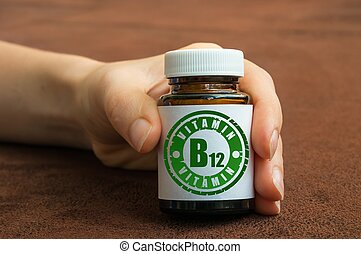 Human hand holding a bottle of pills with vitamin B12 on ...