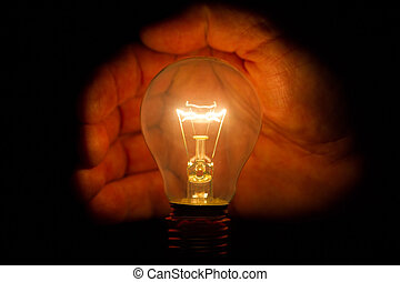 Human hand holding a light bulb to conserve energy darkness