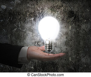 human hand holding brightly light bulb illuminated dark old wall