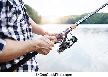 Human hand holding fishing rod