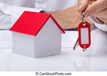 Hand Holding House Keys With House Model