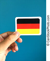 Human hand holding small card with national flag of Germany
