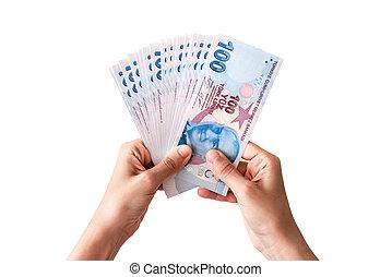 Human hand holding Turkish money. Isolated on white background.