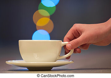 Human hand holding white cup of coffee with colorful bokeh steam