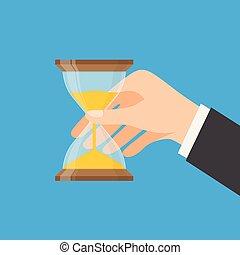 Human hand holds a hourglass.