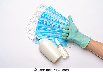 Human hand in protective glove, face protective masks and hand sanitizer or liquid soap isolated over light grey background