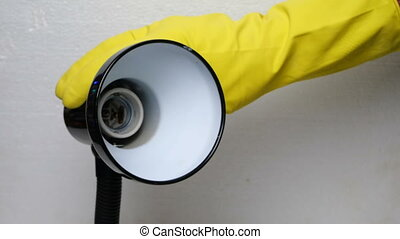 Human hand in yellow rubber glove unscrews damaged light bulb from the base of a desk lamp.