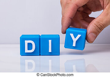Human Hand Making Word Diy With Blue Cubic Blocks