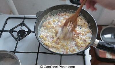 Human hand mixes food with wooden shovel.