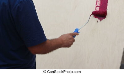 Human hand painting with roller in hand. Coloring red paint...