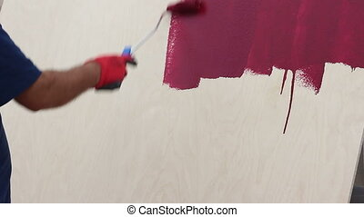 Human hand painting with roller in hand.