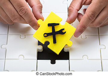 Human hand placing last yellow piece into jigsaw puzzles